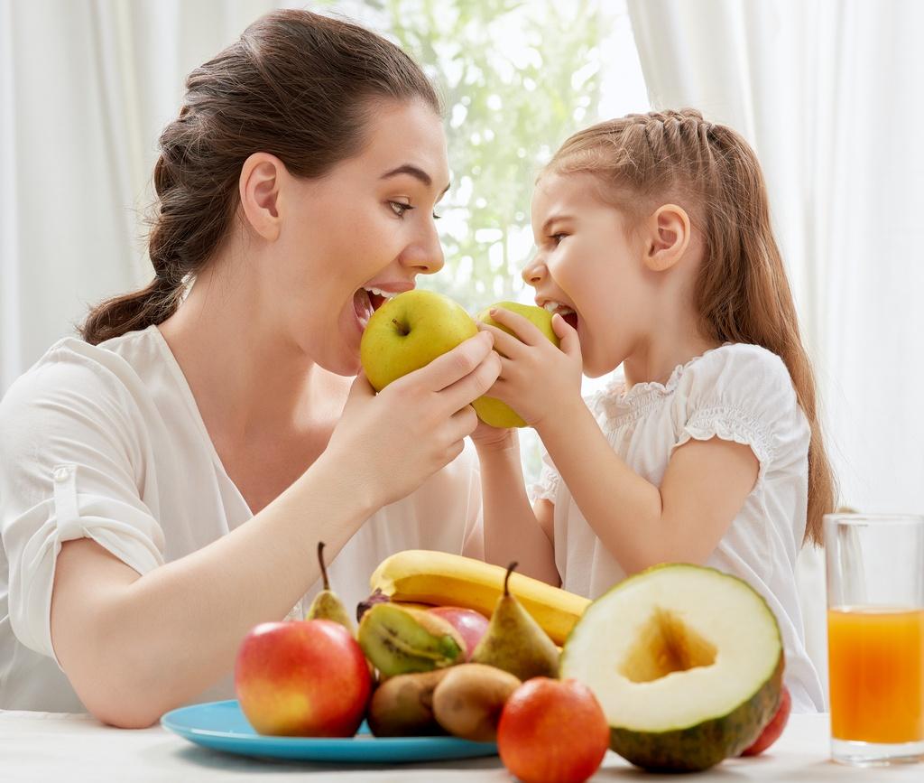 happy family eating fresh fruit